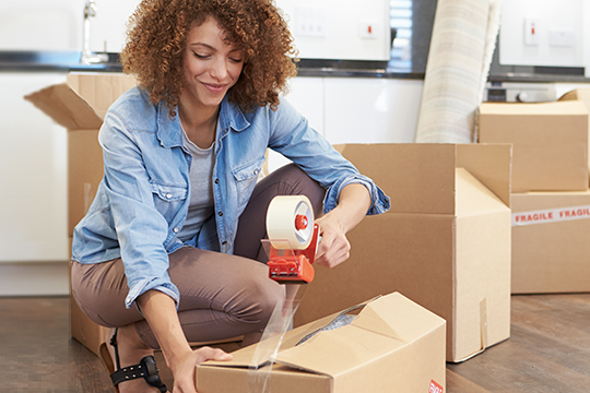 Woman packing up boxes in her home
